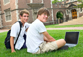 Two students sitting on grass with a laptop